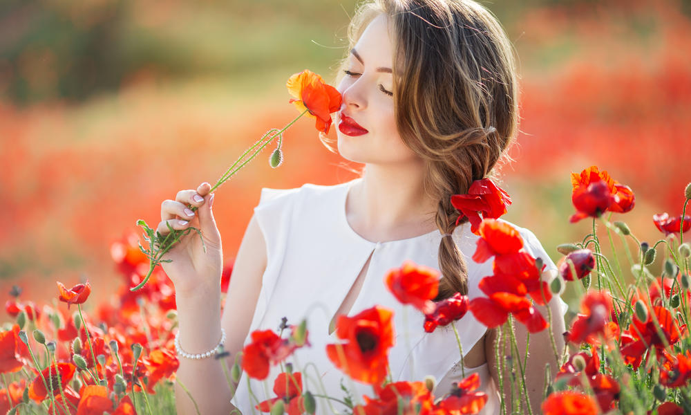 Beautiful young girl with fashion makeup in field of red poppy flowers, spring time